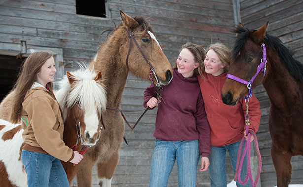 Three girls outside with their horses